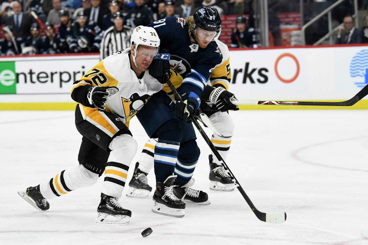 Winnipeg Jets' Kyle Connor (81) and Pittsburgh Penguins' Patric Hornqvist (72) battle for the puck during second-period NHL hockey game action in Winnipeg, Manitoba, Sunday, Oct. 13, 2019. (Fred Greenslade/The Canadian Press via AP)