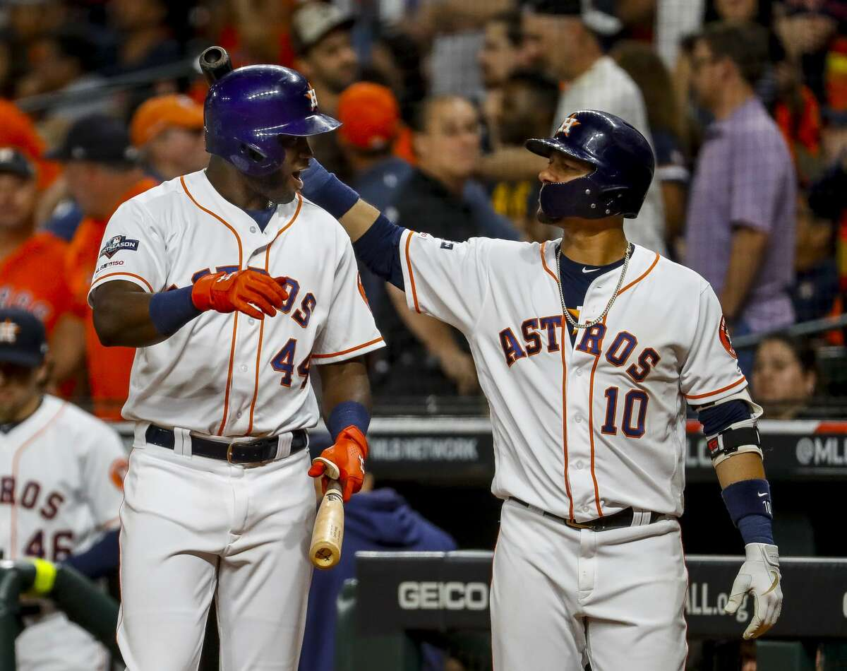 Houston Astros first baseman Yuli Gurriel (10) thumps designated hitter Yordan Alvarez (44) on the head before Alvarez goes to bat with two on and one out in the tenth inning of Game 2 of the American League Championship Series at Minute Maid Park on Sunday, Oct. 13, 2019, in Houston.