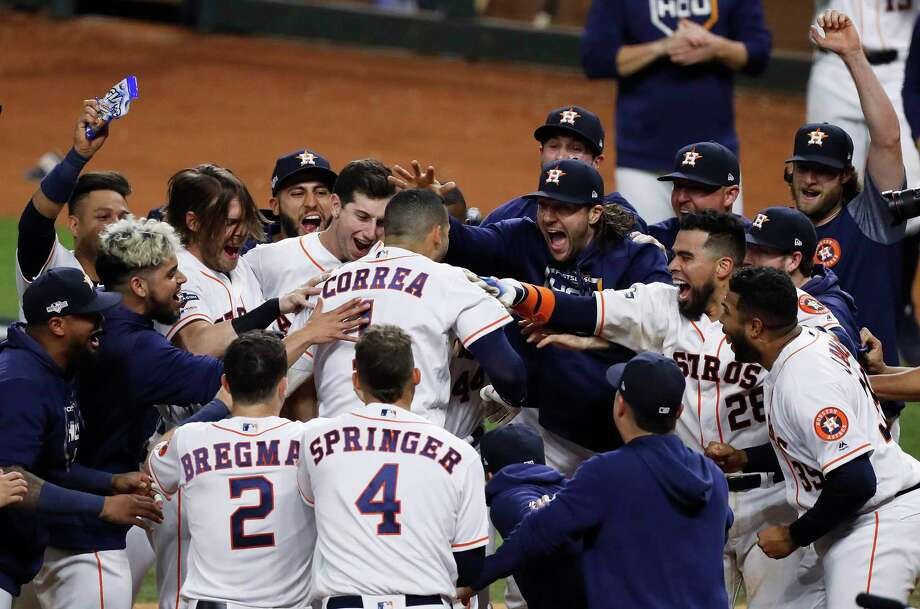 Houston Astros shortstop Carlos Correa is mobbed by his teammates at home plate after hitting a walk-off home run off New York Yankees pitcher J.A. Happ during the 11th inning in Game 2 of baseball's American League Championship Series in Houston on Sunday, Oct. 13, 2019. Photo: Kevin M. Cox, MBR / Associated Press / © 2019 Kevin M. Cox/The Galveston County Daily News