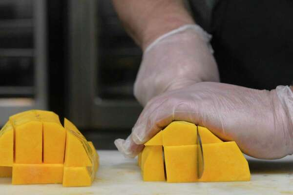 Walter Coffey prepares locally grown butternut squash to be roasted and served for lunch at New Milford High School. The squash was grown at Kimberly Farms, in New Milford. Coffey is assistant manager of the high school cafeteria. 25 percent of the schools' food in New Milford is coming from local farms and producers this week as part of a statewide campaign to serve local food. Friday, October 11, 2019, in New Milford, Conn.