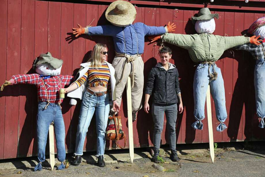 Maddie Lamothe of Boston, left, and Katie Curnan of Bridgeport, pose with scarecrows at the Wakeman Town Farm Oktoberfest on Saturday, Oct. 12, 2019, in Westport, Conn. Photo: Jarret Liotta / Jarret Liotta / ©Jarret Liotta