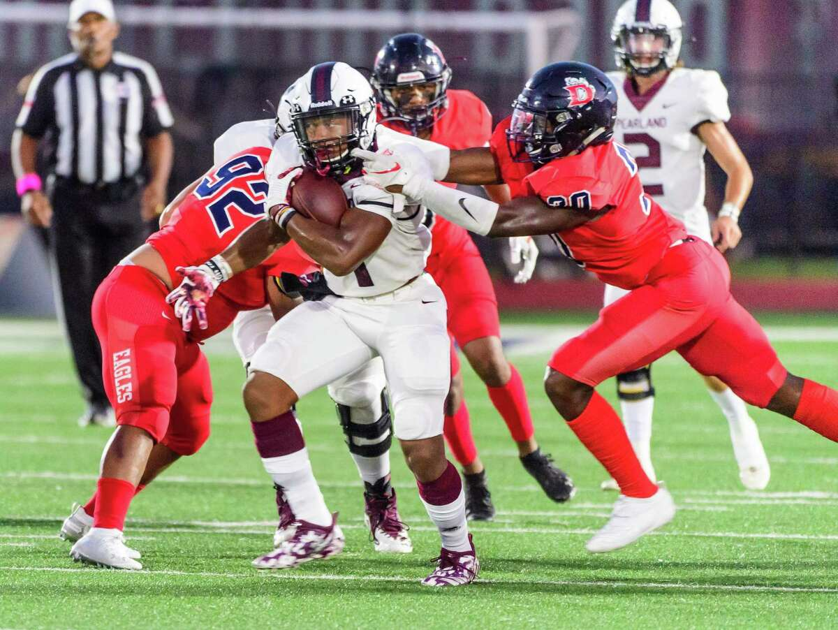 Pearland's Brandon Campbell tries to move past Dawson's defense during their recent encounter. Both teams easily won on Friday to continue a path toward the playoffs.