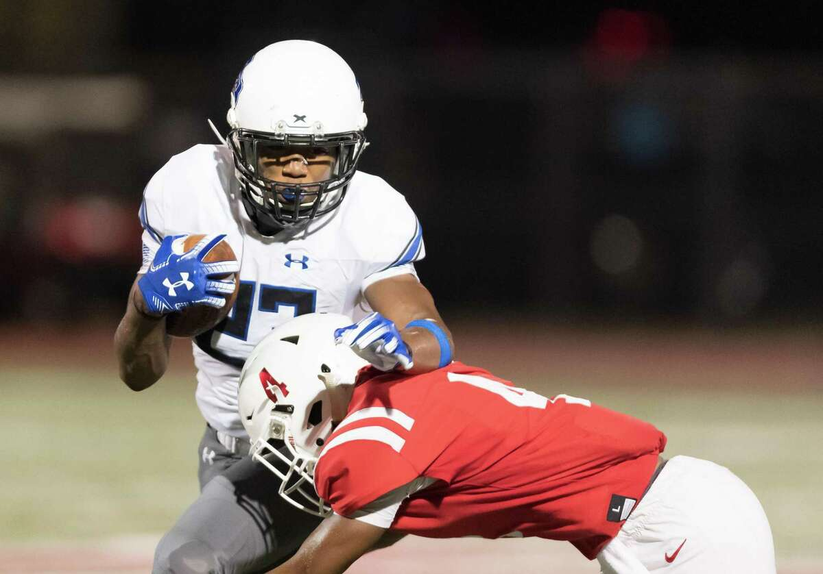 Trinity Christian Tigers Running Back, Dez Moultrie (23) is brought down by St. Thomas Eagles Defensive Back, Cameron Bonner (4) after a short gain in the first half of a high school football game on Friday, September 27, 2019 at St. Thomas High School's Granger Stadium in Houston Texas.