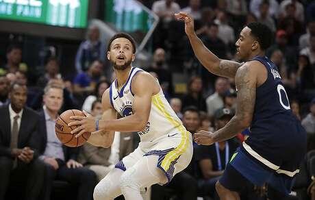 Golden State Warriors' Stephen Curry, left, looks to shoot against Minnesota Timberwolves' Jeff Teague (0) during the first half of an NBA preseason basketball game Thursday, Oct. 10, 2019, in San Francisco. (AP Photo/Ben Margot)