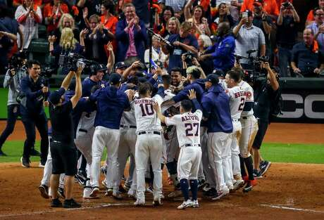 The Astros celebrate with Houston Astros shortstop Carlos Correa (1) after he hit a walk off home run in the eleventh inning to win Game 2 of the American League Championship Series at Minute Maid Park on Sunday, Oct. 13, 2019, in Houston.