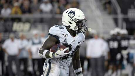 Connecticut running back Kevin Mensah (34) rushes for yardage during the first half of an NCAA college football game against Central Florida Saturday, Sept. 28, 2019, in Orlando, Fla. (AP Photo/Phelan M. Ebenhack)