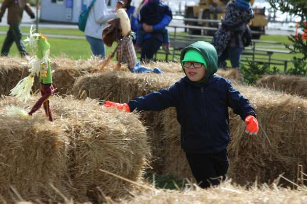 A young visitor to Open Space Park during Fall Festival runs through the straw maze.