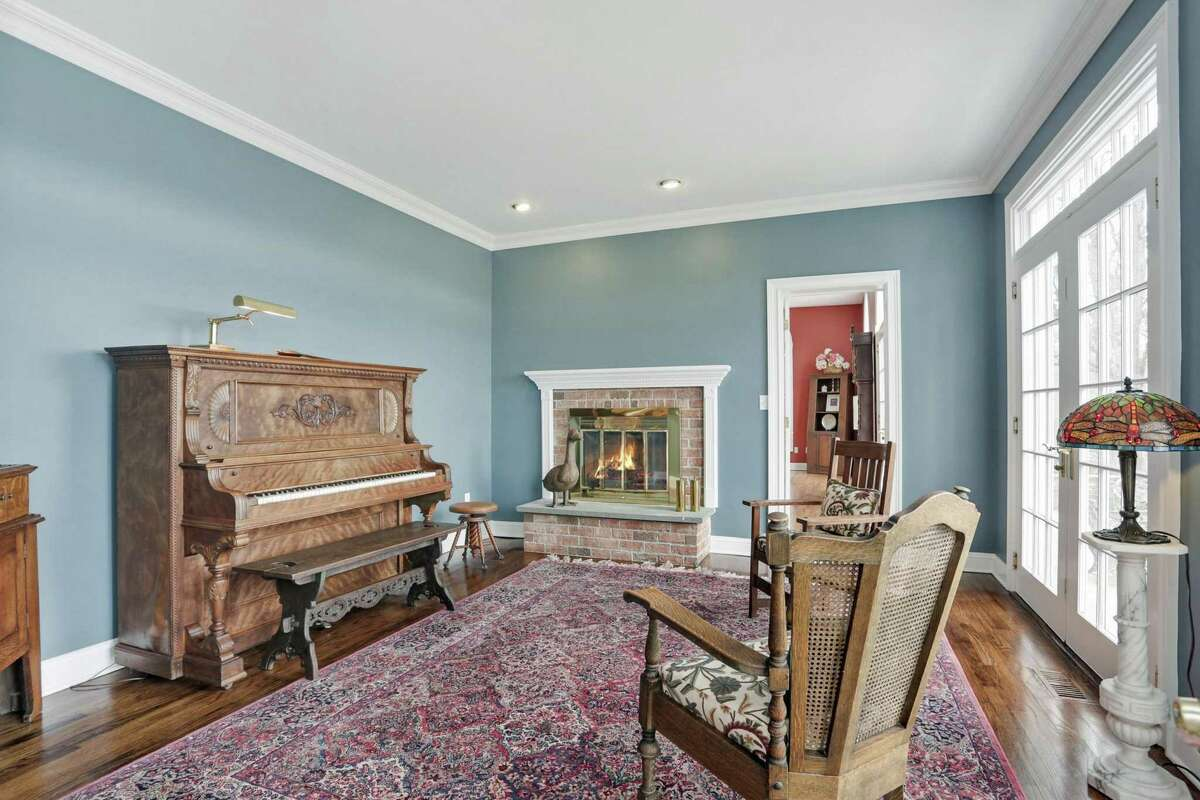 In the living room there is a red brick fireplace with a raised hearth and French doors to the front terrace.