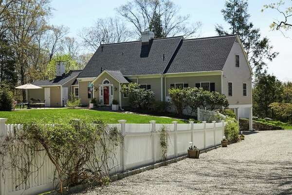 The taupe-colored Cape Cod colonial house at 5 River Road sits on a nearly four-acre property in Lower Weston.