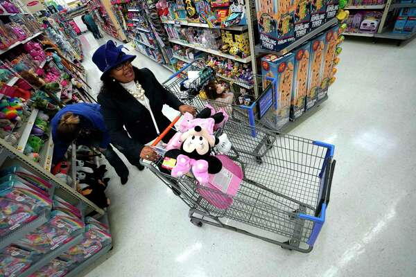 FILE - In this Nov. 9, 2019, file photo shoppers make their way through the toy isles at a Walmart Supercenter in Houston. The National Retail Federation, the nation's largest retail trade group, announced on Thursday, Oct. 3, 2019, that it is forecasting that holiday sales will rise between 3.8% and 4.2% even as uncertainty looms over an escalating trade war with China. (AP Photo/David J. Phillip, File)