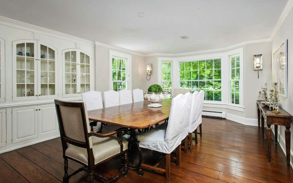 The formal dining room has a bay window, a wall of built-in china cabinetry, and wide-planked hardwood floors.