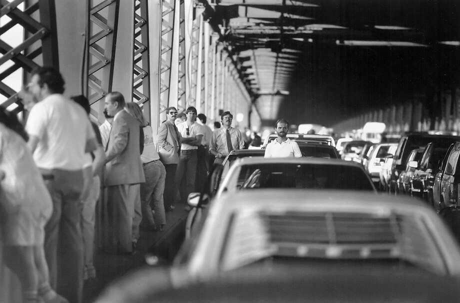People mill around their cars after being stopped by the California Highway Patrol on the Bay Bridge after the Loma Prieta earthquake on Oct. 17, 1989. Photo: Brant Ward / The Chronicle