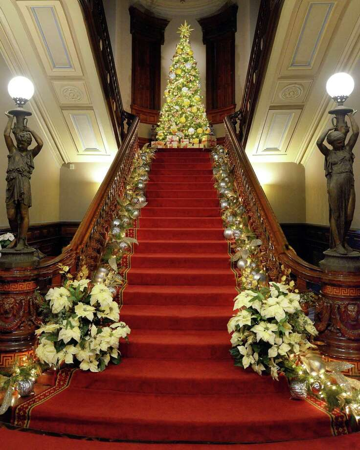 """Norwalk's Lockwood-Mathews Mansion Museum is celebrating the holiday season with """"Toys, Trains, and Magnificent Trees: Illuminating Christmas at the Mansion."""" Staircase decor is designed by Danna DiElsi, of The Silk Touch; the 12-foot-tall tree is designed by Vandamm Interiors. Photo: Gus Apazidis / Contributed Photo"""