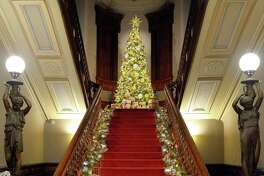 "Norwalk's Lockwood-Mathews Mansion Museum is celebrating the holiday season with ""Toys, Trains, and Magnificent Trees: Illuminating Christmas at the Mansion."" Staircase decor is designed by Danna DiElsi, of The Silk Touch; the 12-foot-tall tree is designed by Vandamm Interiors."