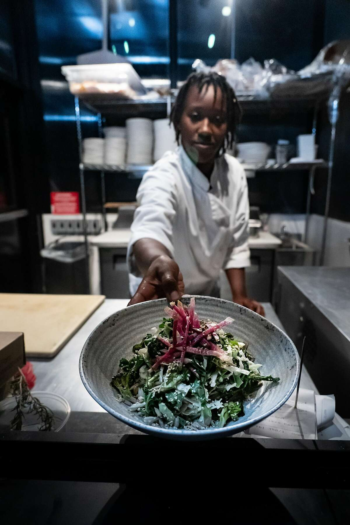 Chef Secret Cammon serves a salad through the window at the Grove at the CIA Copia on Sunday, Sept. 29, 2019, in Napa, Calif.