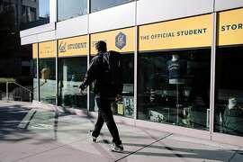 A person walks past the closed Cal Student Store at UC Berkeley in Berkeley, California, on Friday, Oct. 9, 2019.  UC Berkeley canceled classes and closed the school on Wednesday in the face of looming planned power shutoff's by PG&E.