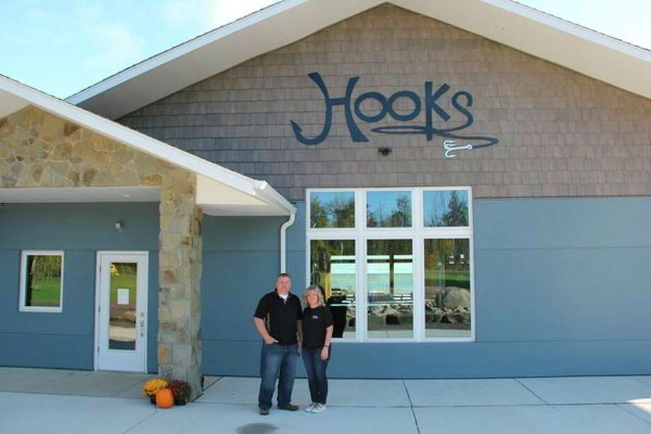 Casey and Tina Jahn out in front of Hooks Waterfront Resort in Harbor Beach. The two converted the former Train Station Motel to Hooks over the summer. (Robert Creenan/Huron Daily Tribune)