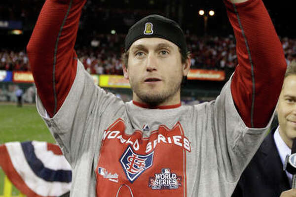 In this Oct. 28, 2011 photo, the Cardinals' David Freese holds up the MVP trophy after Game 7 of the World Series against the Texas Rangers in St. Louis. Freese is retiring at age 36 after a 10-year career.