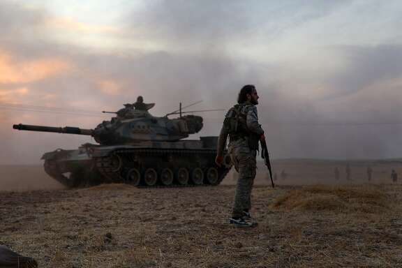 Turkey-backed Syrian fighters gather around a Turkish army US-made M60 tank in the northern outskirts of the Syrian city of Manbij near the Turkish border on October 14, 2019, as Turkey and its allies continue their assault on Kurdish-held border towns in northeastern Syria. - Turkey wants to create a roughly 30-kilometre (20-mile) buffer zone along its border to keep Kurdish forces at bay and also to send back some of the 3.6 million Syrian refugees it hosts. (Photo by Zein Al RIFAI / AFP) (Photo by ZEIN AL RIFAI/AFP via Getty Images)