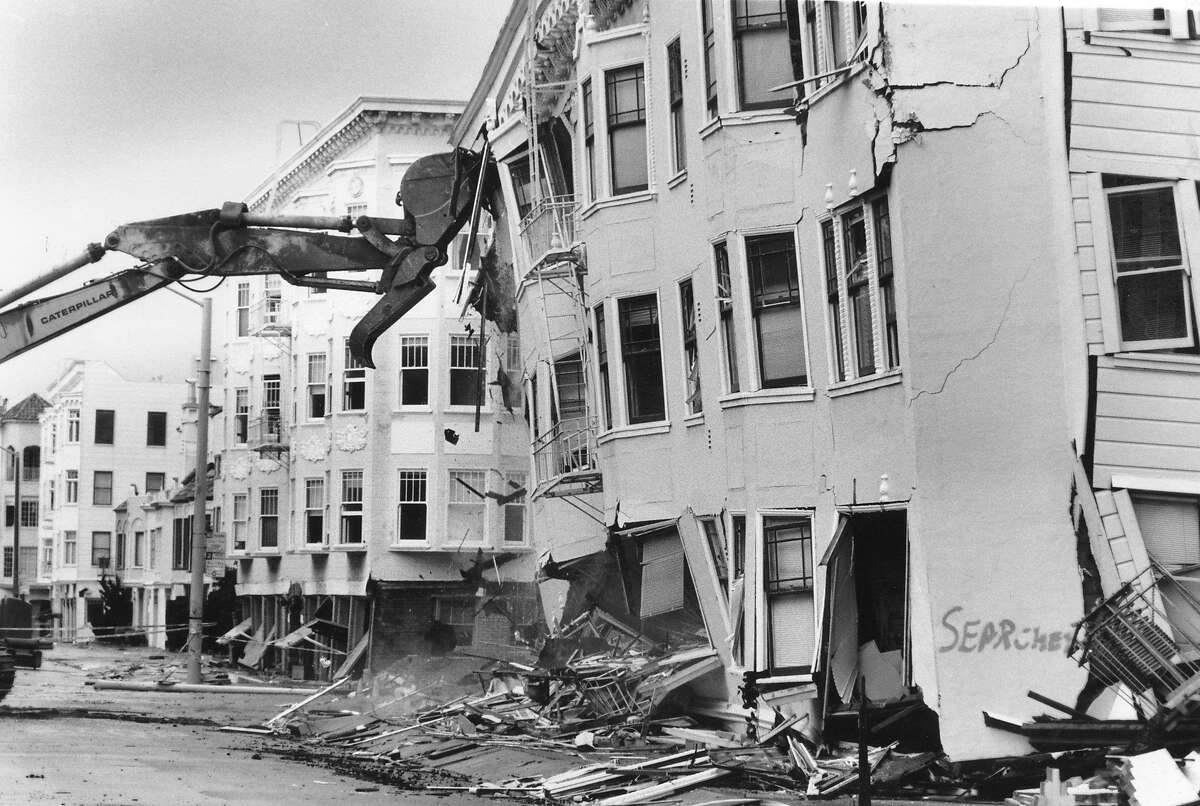 A caterpillar takes works on demolishing a condemned building severely damaged by the Loma Prieta earthquake on Jefferson at Divisidero in the Marina District, Photo taken October 21, 1989