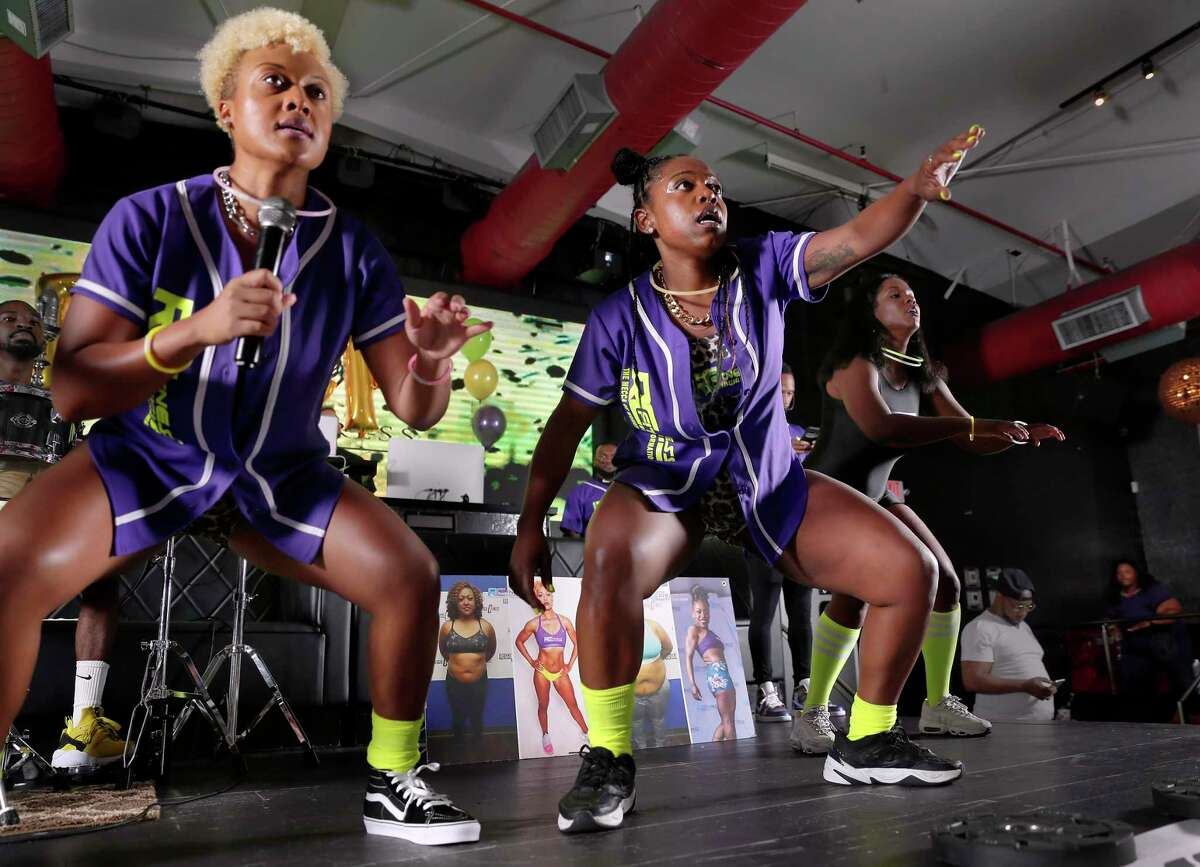 Brianna Marzett, center, who has lost more than 100 pounds and transformed her body through diet and exercise at Reggie C Fitness, works out as well as leads part of the class at the Purple Party Camp, a fitness boot camp held at The Address bar and event venue Saturday, Jul. 20, 2019 in Houston, TX.