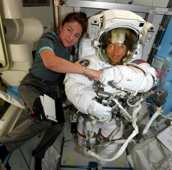 In this image released Friday, Oct. 4, 2019, by NASA, astronauts Christina Koch, right, and, Jessica Meir pose on the International Space Station. The first all-female spacewalk is back on, six months after a flap over spacesuits led to an embarrassing cancellation. NASA announced Friday that the two U.S. astronauts aboard the International Space Station will pair up for a spacewalk later this month. (NASA via AP)