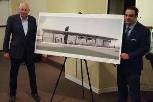 Mercedes-Benz dealer principal Bill Berardino, left, and Manuel Kadre, Mercedes-Benz owner, unveil an illustration of their plans for a dealership in Selma.