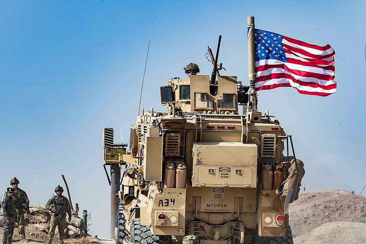 """(FILES) In this file photo taken on October 6, 2019 a US soldier sits atop an armoured vehicle during a demonstration by Syrian Kurds against Turkish threats next to a base for the US-led international coalition on the outskirts of Ras al-Ain town in Syria's Hasakeh province near the Turkish border. - All US troops in northern Syria have been ordered to leave the country in the face of Turkey's attacks on Kurds in the region, a US official said October 14, 2019. Some 1,000 troops will vacate the country, leaving behind only a small contingent of 150 in the southern Syria base at Al Tanf, the official said, one day after President Donald Trump ordered the evacuation.""""We are executing the order,"""" the official told AFP. (Photo by Delil SOULEIMAN / AFP) (Photo by DELIL SOULEIMAN/AFP via Getty Images)"""
