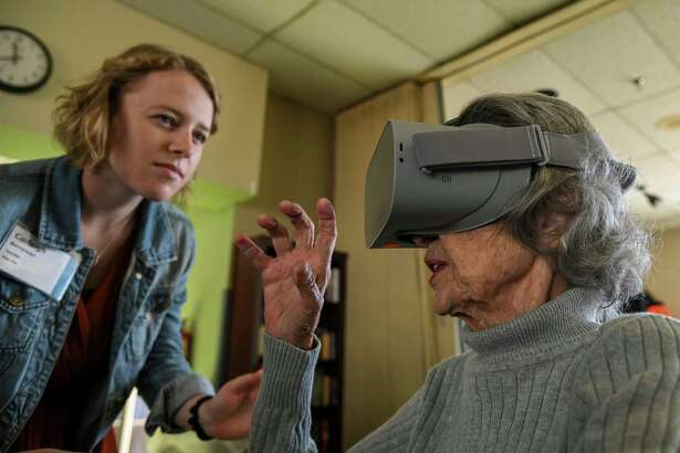 Carleigh Berryman, founder and CEO of Viva Vita, watches as Mary Chiappetta, 89, experiences virtual nature scenes at Powhatan Nursing Home in Falls Church, Virginia, on Thursday, Oct. 10, 2019.