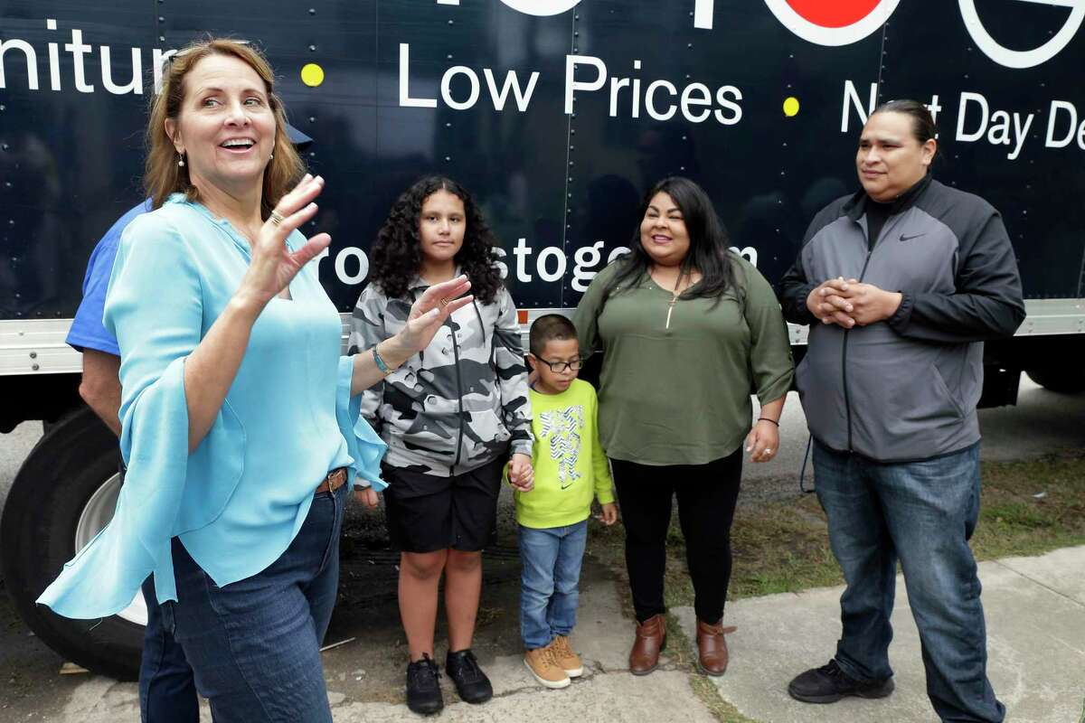 """Laurel D'Antoni greets the Beltran-Martinez family, from left, Samara Martinez, 14, Cesar """"Junior"""" Blas, 9, Cindy Beltran, mother, and Stephen Martinez. SBP repaired the flood-damaged home and the Rockets, Rooms To Go and Marie Flanigan Interiors worked together to finish its interior."""