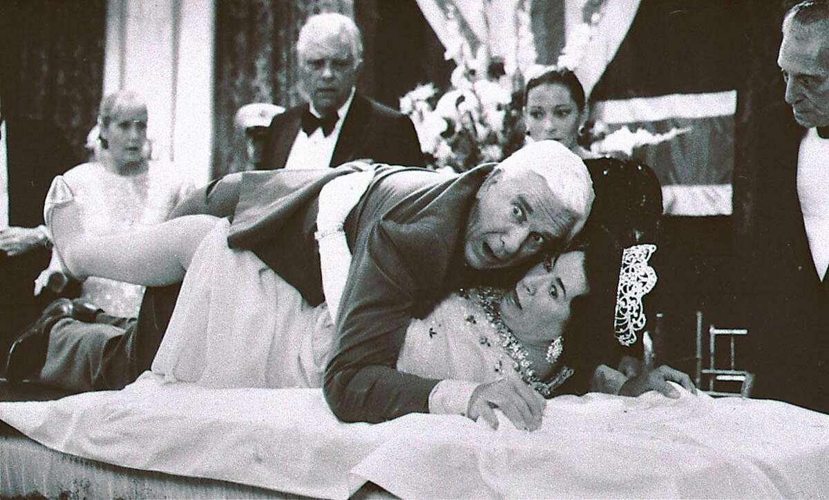 This 1988 publicity file photo provided by Paramount Pictures shows actor Leslie Nielsen, center top, with actress Jeannette Charles, portraying the Queen of England, in a scene from