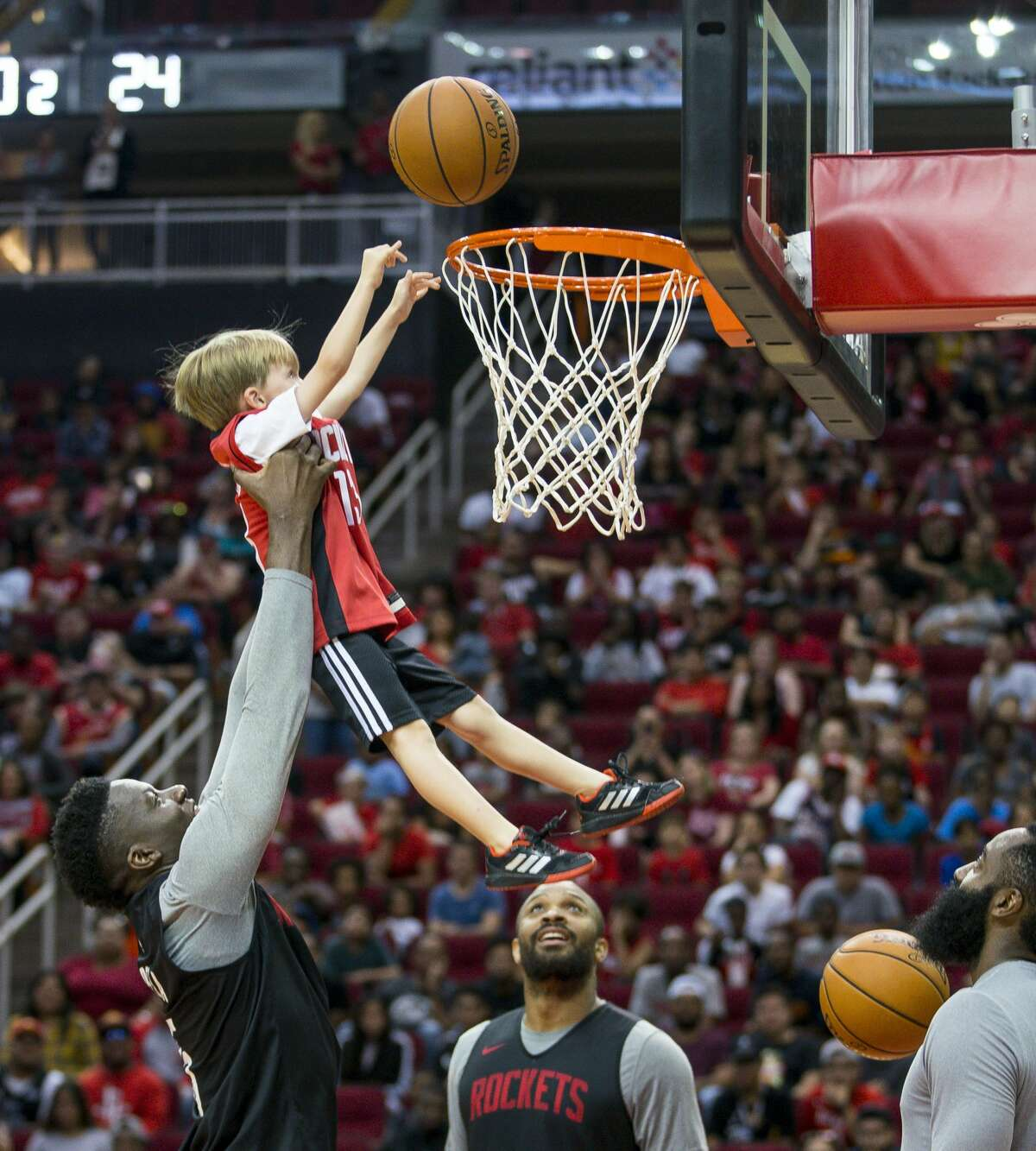 With Houston Rockets guards Eric Gordon and James Harden watching, center Clint Capela picks up six-year-old Houston Radack during a game of knockout with young fans during a Rockets practice open to members of the public at Toyota Center in Houston, Monday, Oct. 14, 2019.