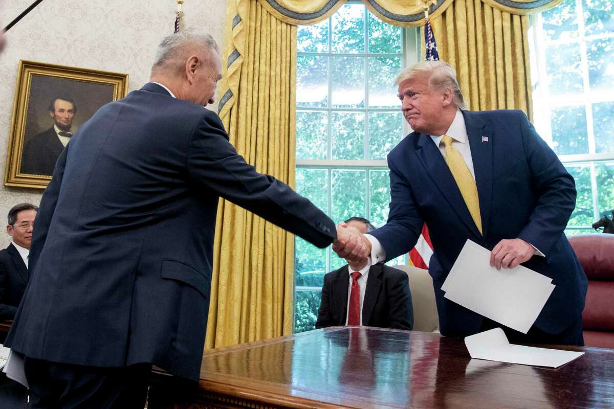 FILE - In this Oct. 11, 2019, file photo, U.S. President Donald Trump, right, shakes hands with Chinese Vice Premier Liu He after being given a letter in the Oval Office of the White House in Washington. China's trade with the United States fell by double digits again in September amid a tariff war that threatens to tip the global economy into recession. (AP Photo/Andrew Harnik, File)