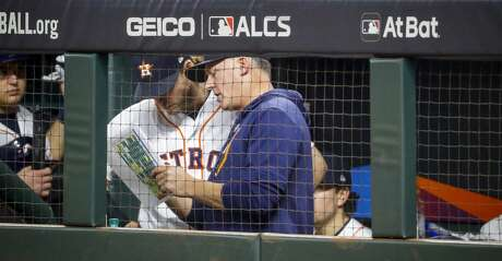 Houston Astros manager AJ Hinch (14) talks to Josh Reddick (22) in the dugout during the fifth inning of Game 2 of the American League Championship Series at Minute Maid Park on Sunday, Oct. 13, 2019, in Houston.