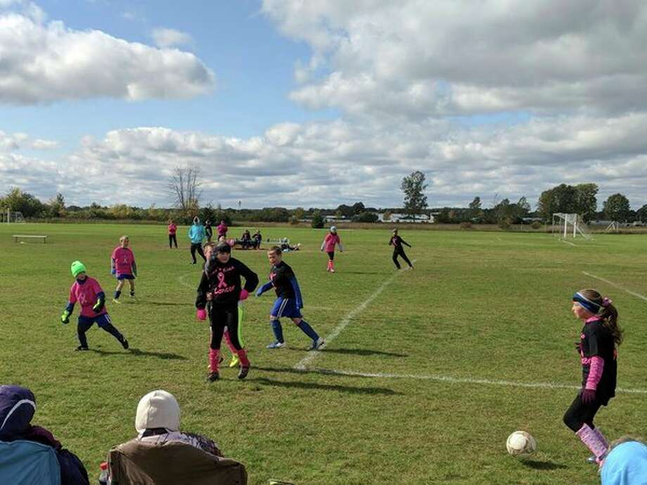 "The whipping wind and 39-degree weather on Saturday didn't stop Gladwin Soccer Teams 1 and 2 from ""kicking cancer."" Both teams wore pink at their game to support breast cancer awareness. Logan Trevillian, 10, who plays for Team 2, helped organize the event and designed the jerseys worn by both teams. Trevillian has lost relatives to breast cancer and recently learned that another aunt is undergoing treatments for it. Team 1 beat Team 2 by a score of 4-3 at the Gladwin County Sports Complex. (Photos by Tereasa Nims for the Daily News)"
