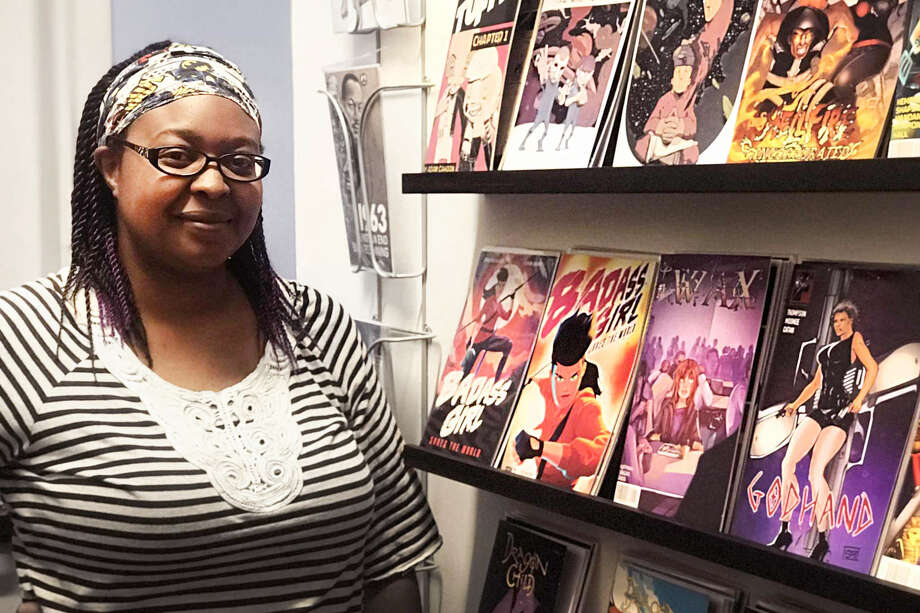 Smith stands in front of some of the independent comics she has for sale. The works are exclusively by local artists, women and people of color. Photo: Amanda Bartlett