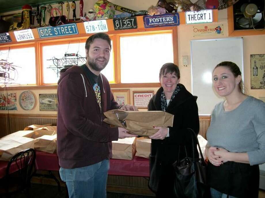Photo by Lynn Fredricksen Mary Victory, of Cheshire, picked up her order of chicken wings from bartender J.P. Higgins at the Side Street Grille in Hamden on Sunday afternoon. Also pictured is server Alyssa Maresco who was busy working on to-go orders.