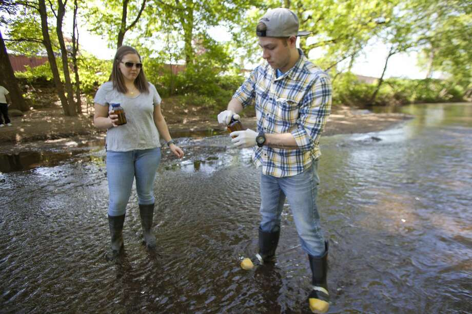Submitted Photo Courtney McGinnis, left, assistant professor of biology at Quinnipiac University, and student John Chiari of Wallingford have started an eight-week study that will identify and quantify known pollutants in water from the Quinnipiac River.