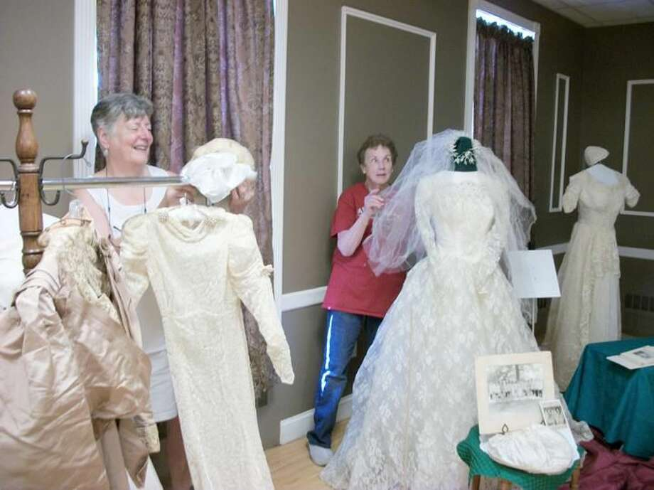 """Photo by Lynn Fredricksen Historical Society members Julie Hulten (right) and Ann Clark (left) put the finishing touches on two of the many wedding gowns that were displayed at the Historical Society's program, """"Wedding Gowns Through the Ages."""" The event drew a huge crowd to the Masonic Lodge on Church Street Sunday afternoon."""