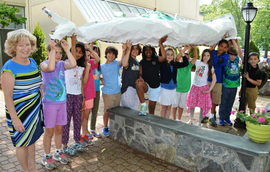 Submitted Photo Fourth-graders and their teacher, Sara Dixon, pictured left, show off a 13-foot stuffed whale that students scaled to size over the past month in their math classes. Students of all ages helped decorate the scaled whale during the school's Mystic Seaport Festival.