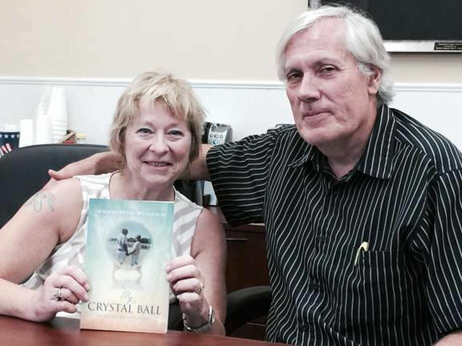 """Submitted Photo Deborah Wilton McLoughlin and her husband, Bernie McLoughlin, pose with a copy of her new book, """"My Crystal Ball: The Invisible Side of Parkinson's,"""" which she penned after being diagnosed with Parkinson's Disease at age 49."""