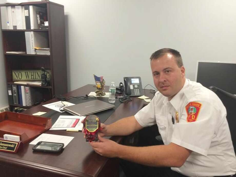 Photo by Lynn fredricksen North Haven Fire Chief Paul Januszewski displays an antique fire extinguisher that works when the glass is broken to release a chemical that puts out the fire. Fire Prevention Week runs from Oct. 4 to 10 with local firefighters visiting schools throughout town.