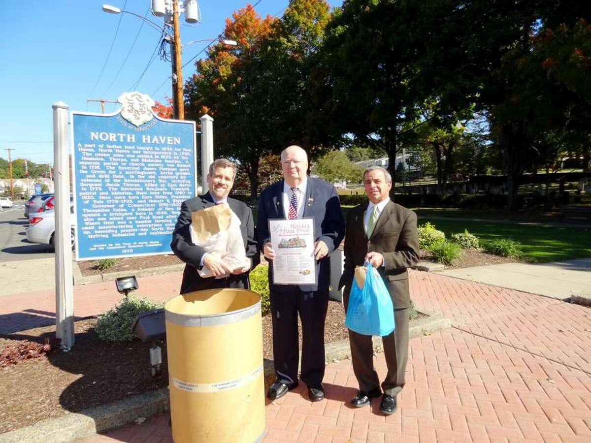 Submitted Photo Left to Right, Reverend Scott Morrow, Town of North Haven Welfare Administrator, Dan Riccio, North Haven First Selectman, Michael J. Freda kick off the Holiday Food Drive outside of Town Hall on Oct. 15.