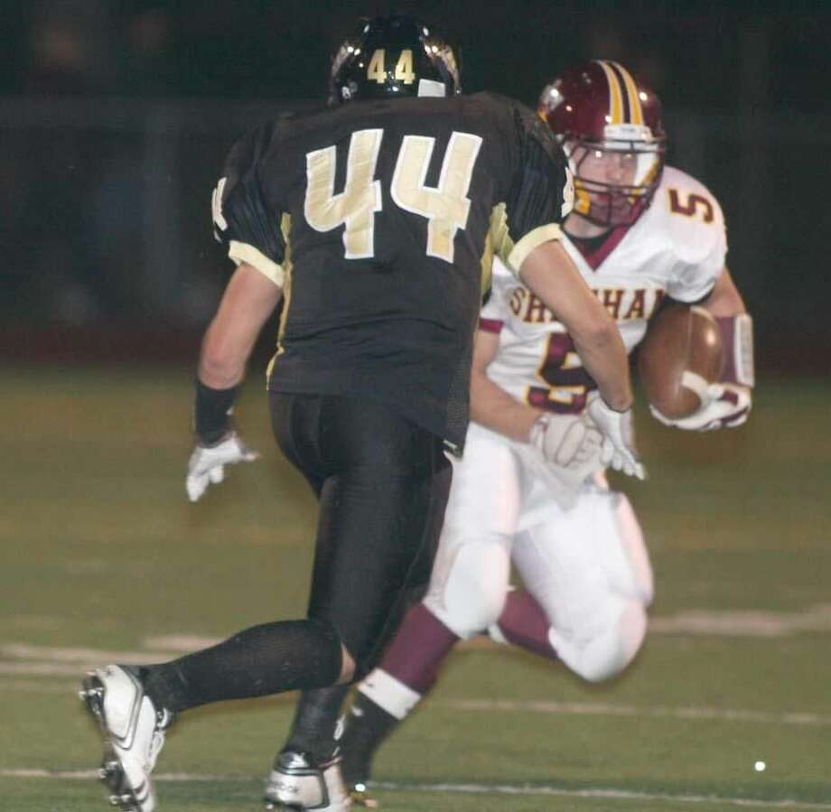 Sheehan's Zach Prefontaine runs past Law's James Quish in a game played earlier this season. Prefontaine led the Titans with 79 yards rushing in their 40-7 loss to New London. (Photo by Russ McCreven)