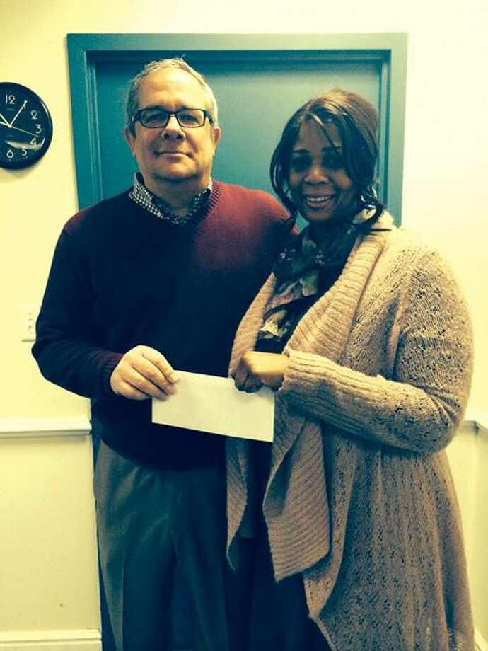 Submitted Photo Steve Savino, WQUN's assistant general manager, presents a $1,000 check to Darlene Butler, community services director for the town of Hamden. The money was raised through the fourth annual Hamden Senior Holiday Gift Run.