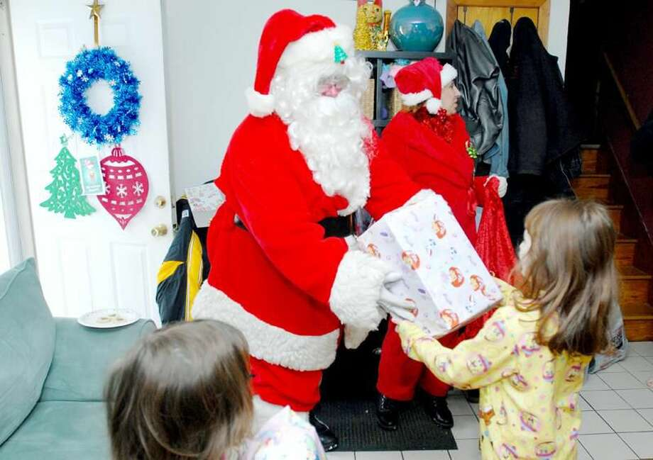 Photo by Arnold Gold Mark Powell of the Northeast Volunteer Fire Association dressed as Santa Claus gives gifts to Sierra Ciak (left foreground), 4, and her sister, Savannah Ciak (right), 5, at their home in North Haven Sunday. In the background is Julie Wisneski.