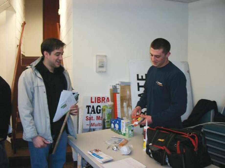 By Lynn Fredricksen Hamden resident Robert Roman (left) gets some energy saving tips from Lantern Energy technician Dylan Cruz at an energy forum at the North Haven Memorial Library last week. Presented by the North Haven Clean Energy Task Force, the program aimed to encourage property owners to sign up for an energy audit of their home.