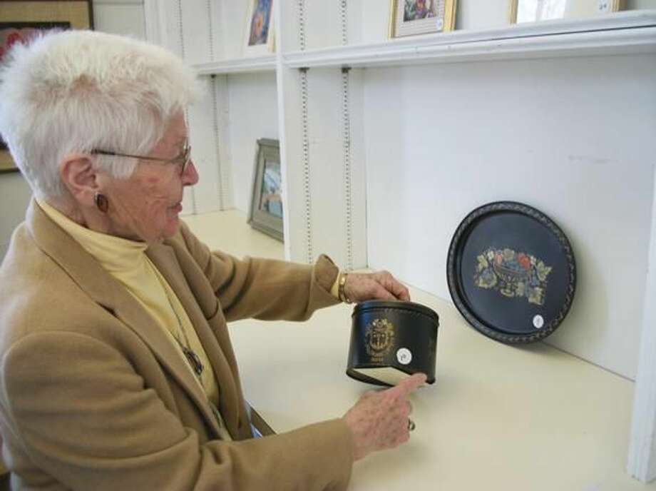 Photo by Lynn Fredricksen Betty Baptie, a longtime member of the North Haven Art Guild, shows a tobacco canister she hand painted as a gift for her father many years ago. In the background is a tray she hand painted for her son. Baptie's creations are part of a month-long show celebrating women artists.