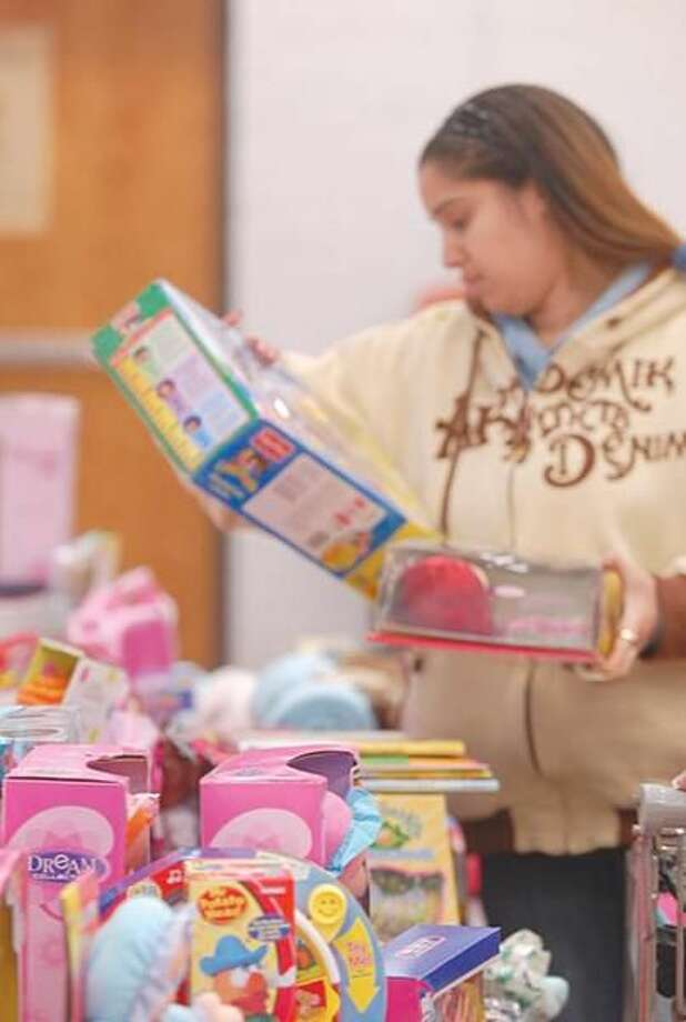 Photo by Joseph Cole Jacklyn Rodriguez selects presents at the Hamden toy distribution at the Keefe Center on Friday.