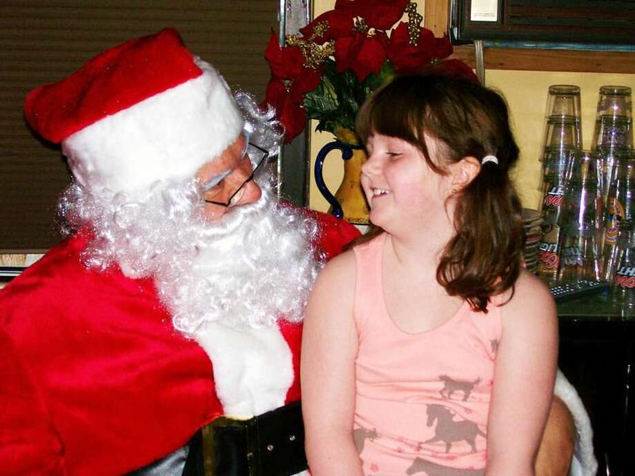 "Submitted Photo Olivia Markar tells Santa what she would like for Christmas at the ""Lunch with Santa"" hosted by Wallinford Dream Foundation and SabbaticAl's Restaurant."